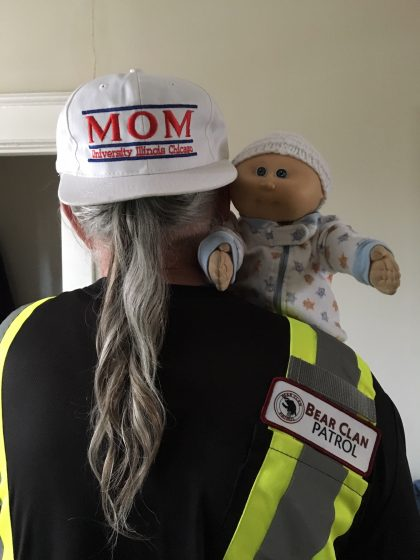 "man holding doll and wearing cap with ""mom"""