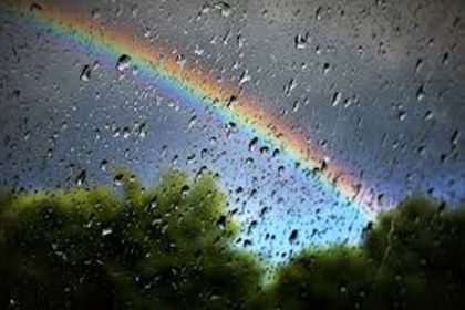 rainbow seen through wet glass on rainy day
