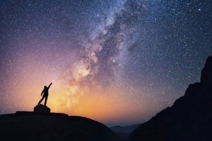person reaching toward the night sky and the milky way