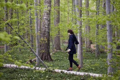 woman walking through woods balancing on a log