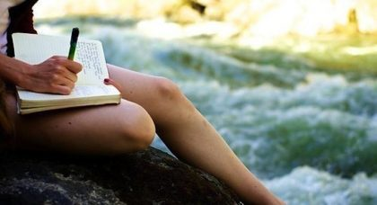 woman writing in notebook by river
