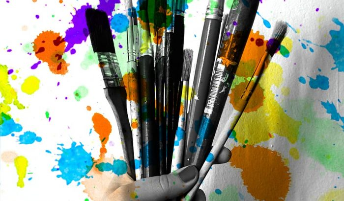 woman's hand holding paint brushes