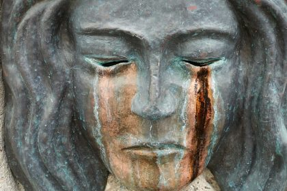 bronze statue of face crying