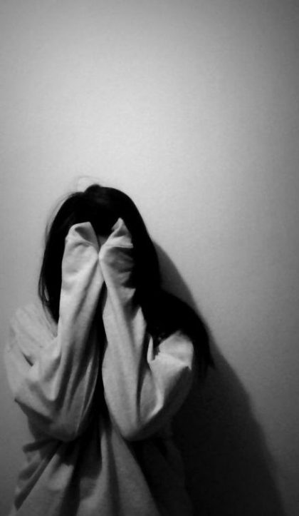 woman covering her face with her arms