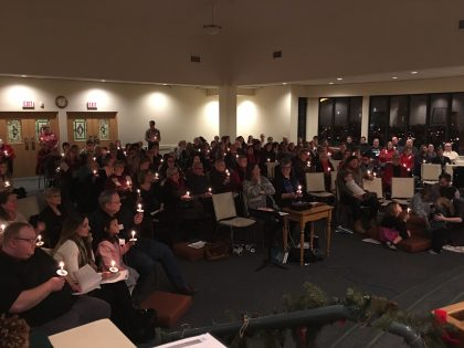 The congregation sings Silent Night together by candlelight on Christmas Eve