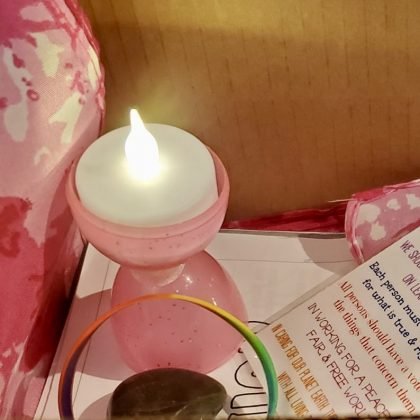 a tiny pink plastic chalice made from an Easter egg, with a lit tea light inside