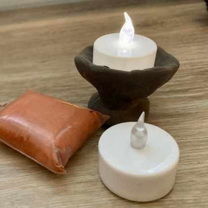 a small home-made black clay chalice, with a lit tea light inside and supplies nearby
