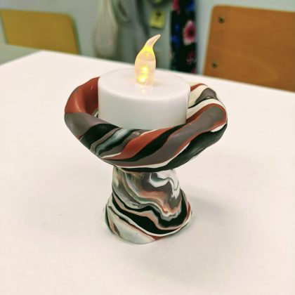 a small chalice made of fimo, with a lit tea light inside