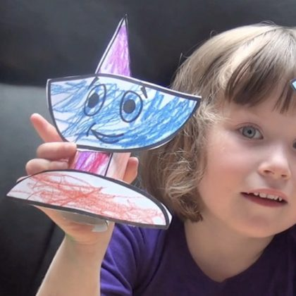 A child holding a paper chalice, coloured with bright crayons