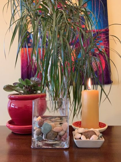 bowl of water with stones, lit candle in chalice bowl, and plants