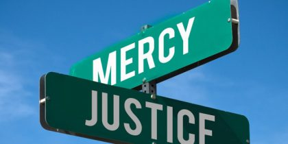 two street signs at the corner of justice and mercy