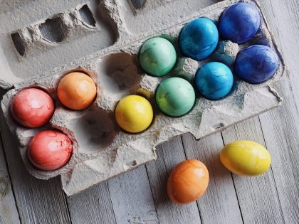 A dozen coloured eggs in and around an egg carton, in six colours of the rainbow.
